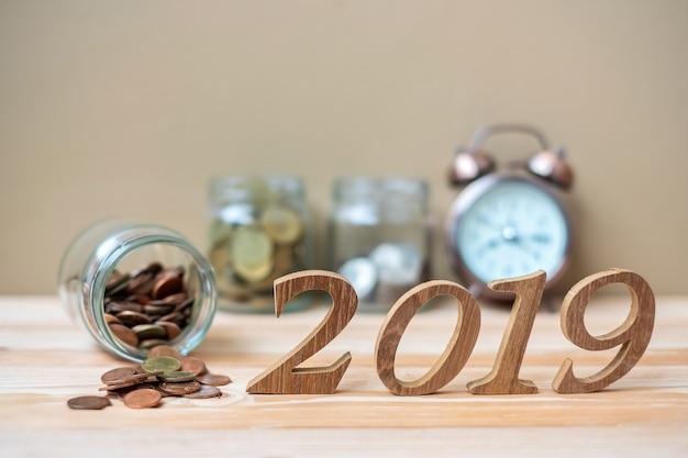 2019 happy new year con pila di monete d'oro e numero di legno