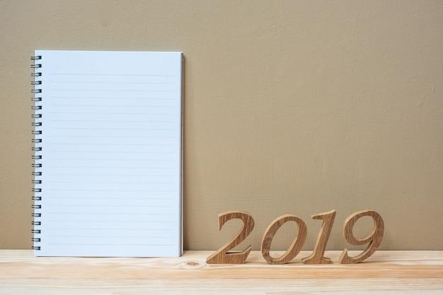 2019 happy new years con notebook e numero di legno sul tavolo