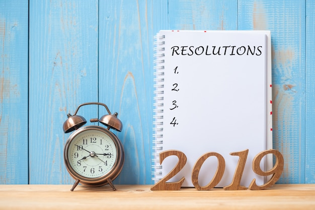 2019 happy new years con risoluzione testo su notebook, retro sveglia