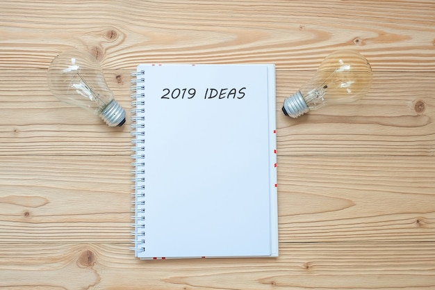 2019 idea con lampadina e carta sbriciolata sul tavolo. anno nuovo inizio