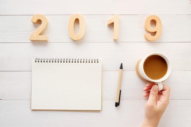 2019 lettere di legno, carta del taccuino in bianco e tazza di caffè della tenuta della mano sul backgro bianco della tavola