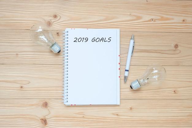2019 obiettivi con lampadina e carta sbriciolata sul tavolo.