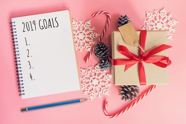 2019 obiettivi, confezione regalo marrone vista dall'alto, taccuino e decorazioni natalizie per il nuovo anno