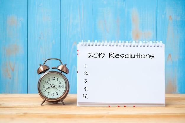 2019 risoluzioni di testo su notebook e retro sveglia sul tavolo e copia spazio