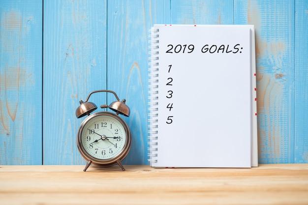2019 testo degli obiettivi su notebook e retro sveglia sul tavolo