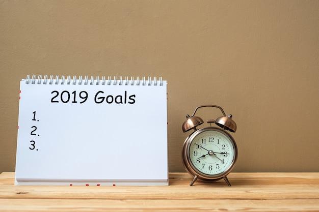 2019 testo di obiettivi su notebook e retro sveglia sul tavolo e copia spazio