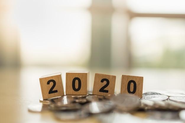 2020 anno nuovo, affari, concetto di risparmio e pianificazione. chiuda in su del giocattolo di legno del blocchetto di numero sul mucchio delle monete con lo spazio della copia