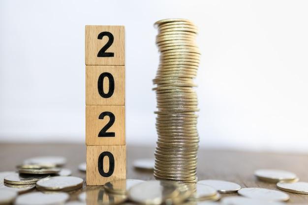 2020 anno nuovo, affari, concetto di risparmio e pianificazione. chiuda su della pila di giocattolo di legno del blocchetto di numero con la pila di monete sulla tavola di legno e sul fondo bianco con lo spazio della copia