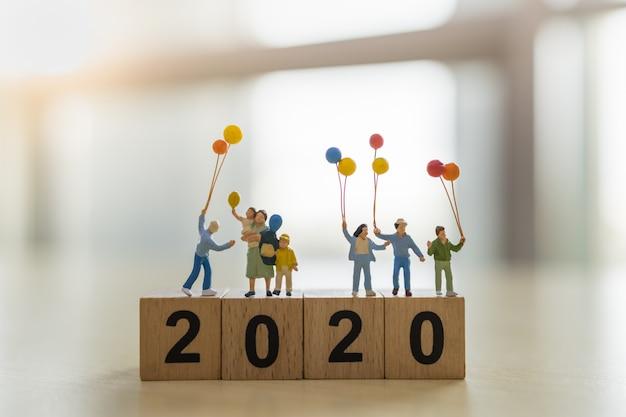 2020 anno nuovo e concetto di famiglia. chiuda in su del gruppo di bambini e figure in miniatura del bambino con l'aerostato sul blocchetto di numero di legno.