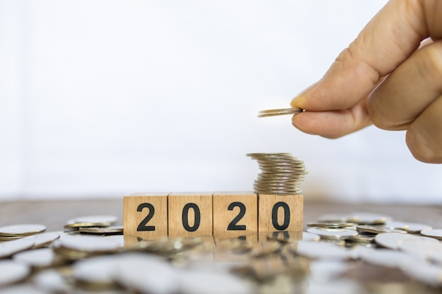 2020 anno nuovo e concetto di risparmio. chiuda su della pila di monete d'argento sul giocattolo del blocco di legno di numero con la tenuta della mano dell'uomo e metta la moneta sopra la pila