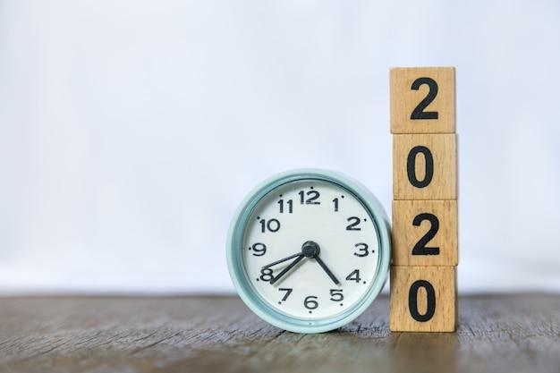 2020 anno nuovo e tempo. chiuda su dell'orologio rotondo e la pila di blocchetti di numero di legno sulla tavola e sul bianco di legno.