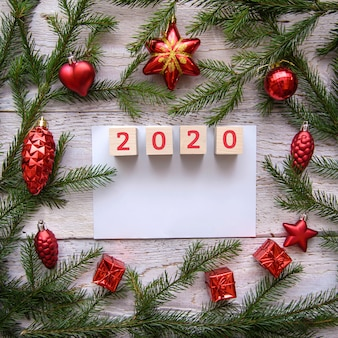 2020 in una cornice di rami di un albero di natale e giocattoli rossi su uno sfondo di legno