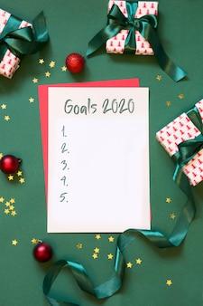 2020 obiettivi del nuovo anno, pianificazione, lista di controllo, lettera a babbo natale, la tua lista dei desideri sul verde. vista dall'alto.