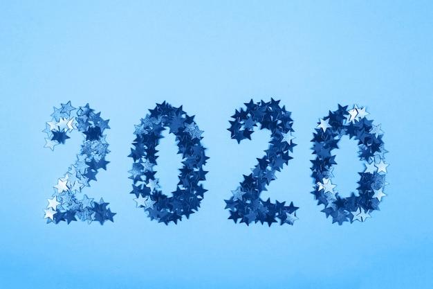 2020 simbolo del nuovo anno di coriandoli d'oro su sfondo blu.