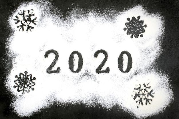 2020 testo fatto con farina con decorazioni su sfondo nero.