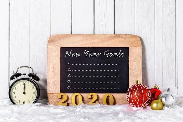 2020 testo in legno con sveglia con ornamenti natalizi e la lista degli obiettivi di capodanno scritti sulla lavagna con pelliccia bianca