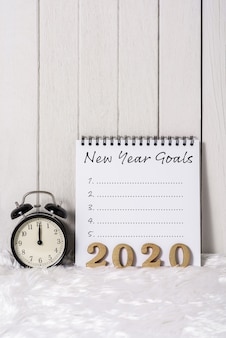 2020 testo in legno e lista degli obiettivi di capodanno scritti su notebook con sveglia