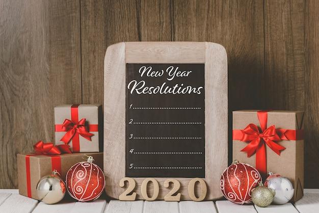 2020 testo in legno e ornamenti natalizi ed elenco delle risoluzioni del nuovo anno scritto sulla lavagna