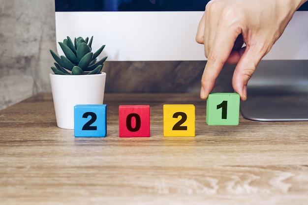 2021 felice anno nuovo, mano che regge blocco di legno sul tavolo da tavolo in legno computer e pianta da vaso. concetto di nuovo anno