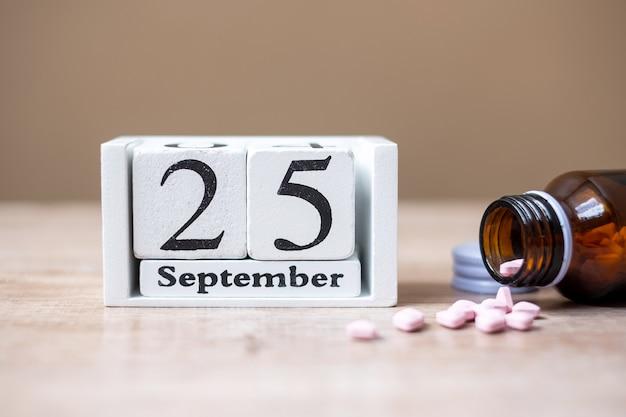 25 settembre del calendario in legno e droga, concetto di giornata mondiale del farmacista