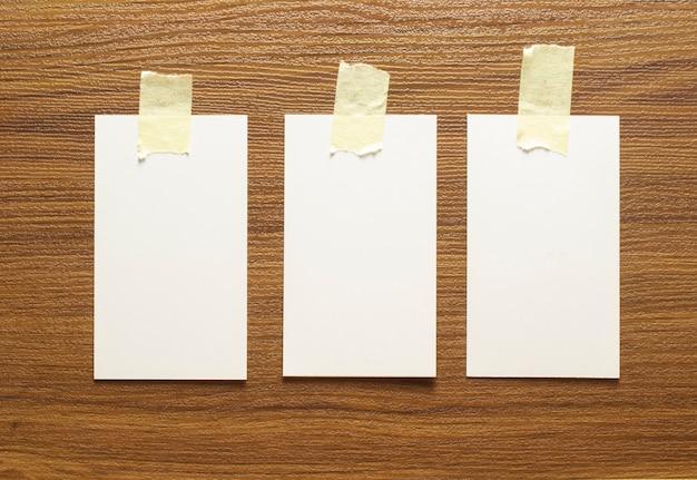 3 biglietti da visita in bianco incollati con nastro giallo su una superficie di legno, dimensioni 3,5 x 2 pollici