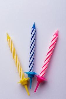 3 candele di compleanno su sfondo bianco. per auguri di compleanno. spazio per inserire testo. molto colorato, con blu, rosso, giallo e bianco.