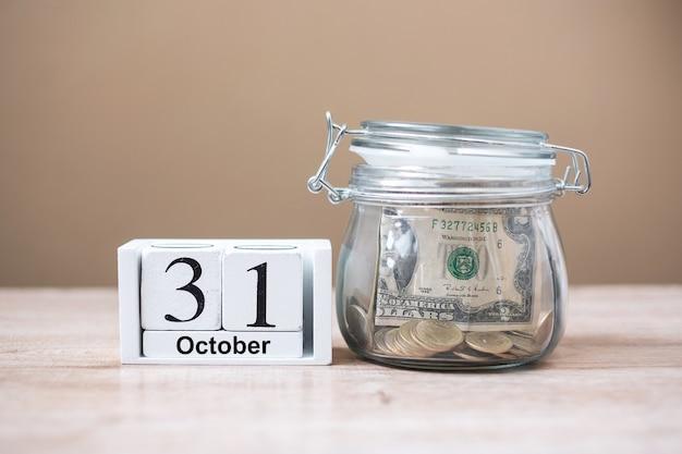 31 ottobre del calendario in legno e denaro in vaso di vetro sul tavolo, giornata mondiale per il risparmio