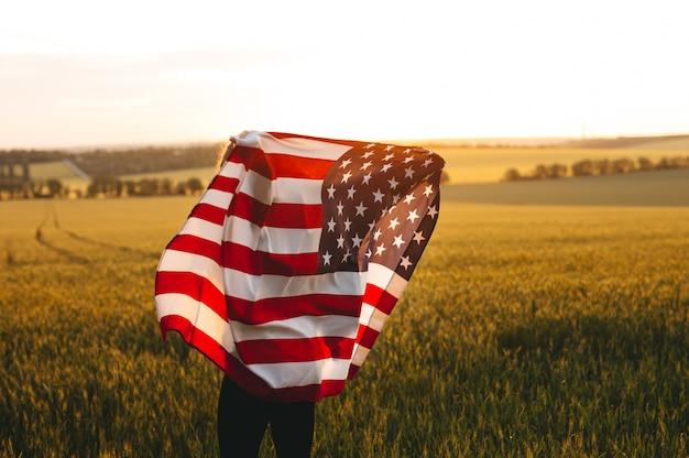 4 luglio. donna con la bandiera americana in esecuzione in un campo di grano al tramonto. festa dell'indipendenza, festa patriottica.