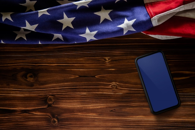 4 luglio o memorial day del concetto degli stati uniti. schermo mobile vuoto per mockup. bandiera usa che si trova sul fondo di legno. simbolico americano. vista dall'alto