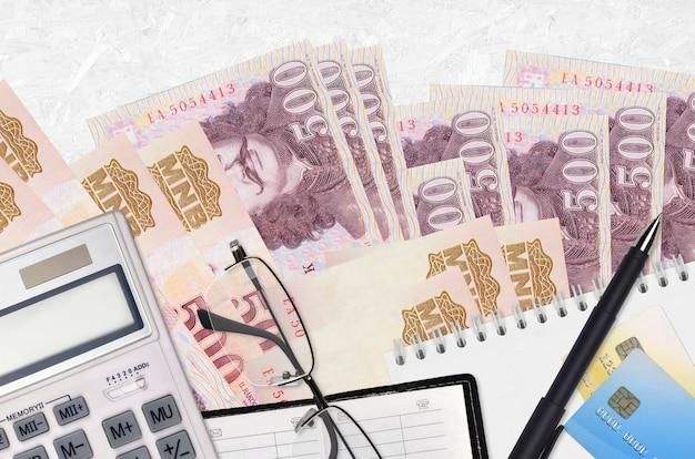 500 banconote in fiorini ungheresi e calcolatrice con occhiali e penna.