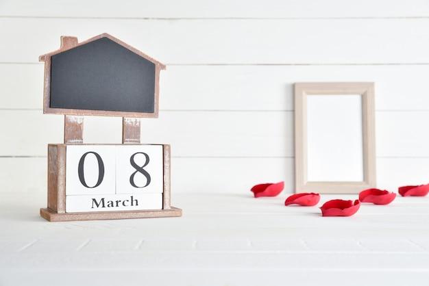 8 marzo calendario di blocco di legno del testo con cornice e petalo di rose rosse