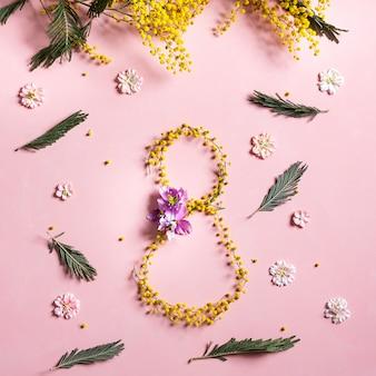 8 marzo carta quadrata su sfondo rosa. bellissimi fiori di mimosa gialli. concetto internazionale di giorno della donna.