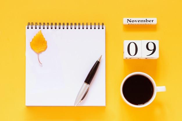 9 novembre tazza di caffè, blocco note con penna e foglia gialla su sfondo giallo