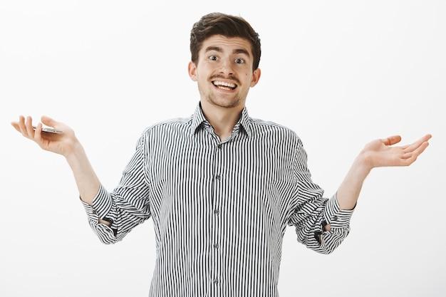 A chi importa cosa succede. ritratto di modello maschio attraente indifferente incurante in camicia grigia, palme aperte e scrollare le spalle felicemente, sorridendo ampiamente e tenendo lo smartphone, in piedi sopra il muro bianco