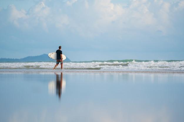 A con un surf tra le mani in riva al mare