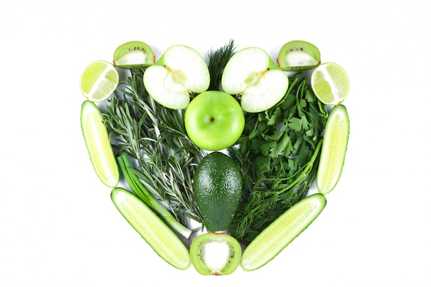 A forma di cuore a base di frutta e verdura verde. cuore fatto da prodotti naturali su sfondo bianco. cuore vegetariano isolato
