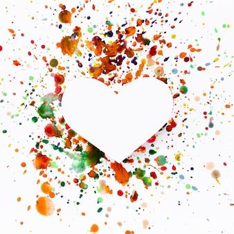 A forma di cuore artistico con macchie di vernice colorata