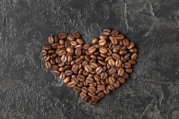 A forma di cuore di chicchi di caffè tostati su sfondo scuro