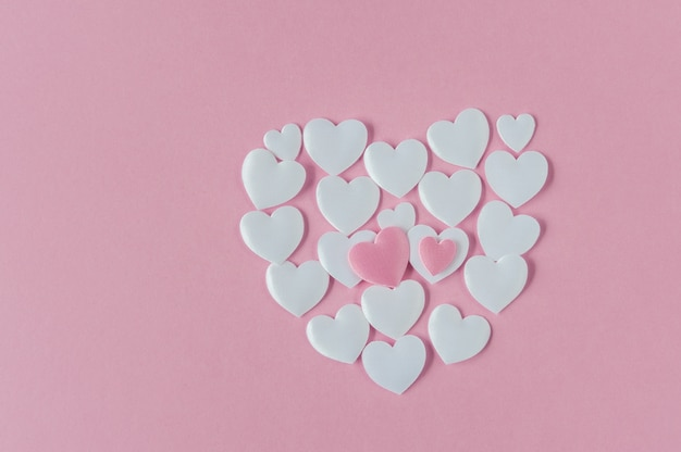 A forma di cuore fatto di cuori di raso bianco su rosa