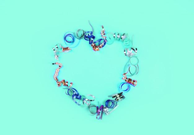 A forma di cuore fatto di serpentino multicolore su uno sfondo di menta.