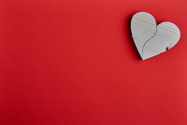 A forma di cuore in legno su carta rossa
