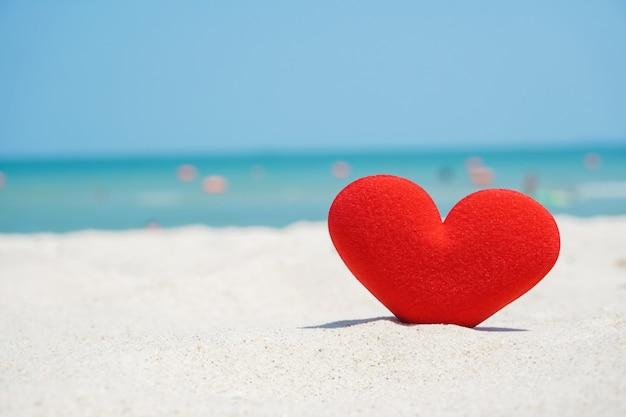 A forma di cuore rosso sulla sabbia della spiaggia, ama il mare
