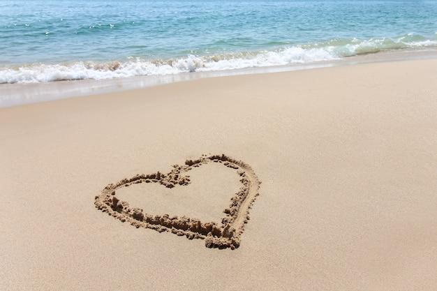 A forma di cuore, simbolo di amore scritto sulla spiaggia di sabbia