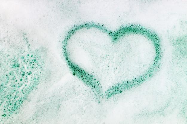 A forma di cuore su sfondo di schiuma di sapone