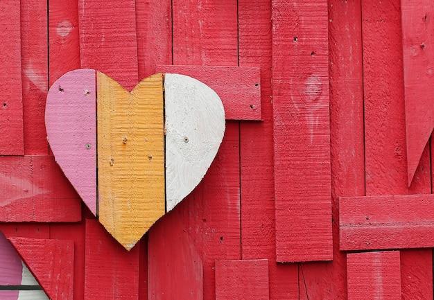 A forma di cuore su sfondo rosso realizzato in legno riciclato per san valentino