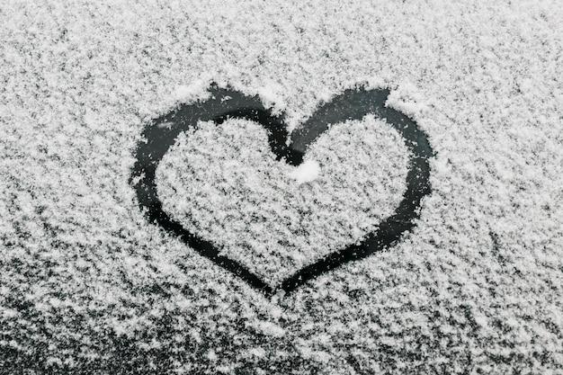 A forma di cuore sul vetro nevoso durante la giornata invernale