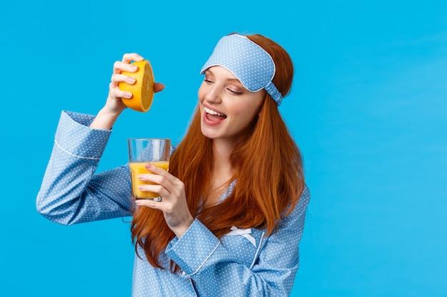 A partire dal mattino sano. glamour ritratto in vita, ragazza piuttosto sexy e femminile, prepara un succo d'arancia fresco, spremi frutta in vetro, sorride, prepara la colazione, indossa maschera per dormire e indumenti da notte
