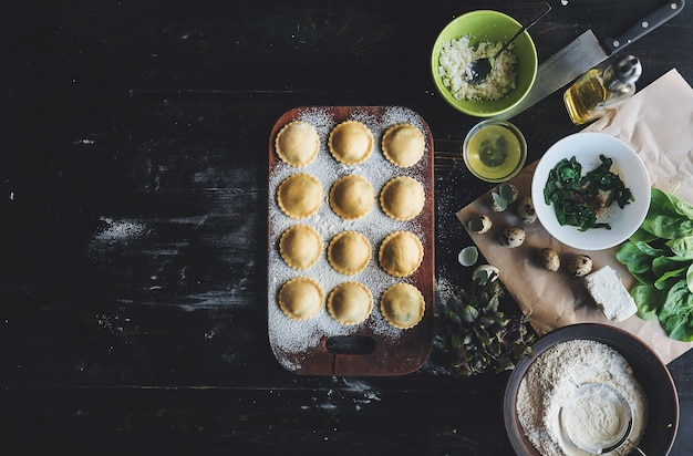 A poco a poco lo chef prepara ravioli con ricotta, tuorli di uova di quaglia e spinaci con spezie. lo chef prepara cucinare i ravioli
