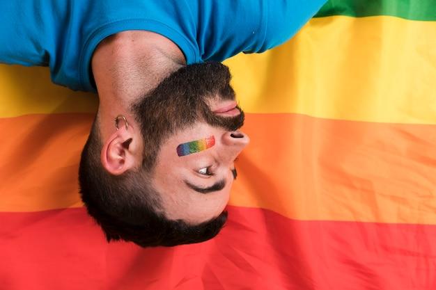 A testa in giù giovane uomo posa sulla bandiera arcobaleno lgbt