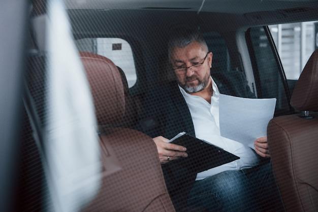 A volte devi portare il lavoro con te. scartoffie sul sedile posteriore della macchina. uomo d'affari maggiore con i documenti